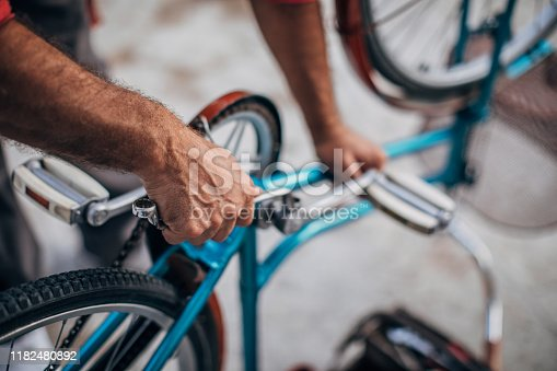 Senior man repairing bicycle in front or back yard
