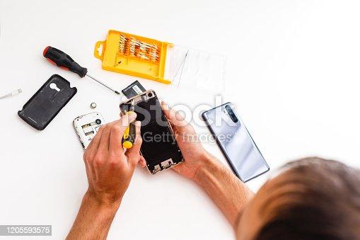 Man repairing broken smartphone in workshop