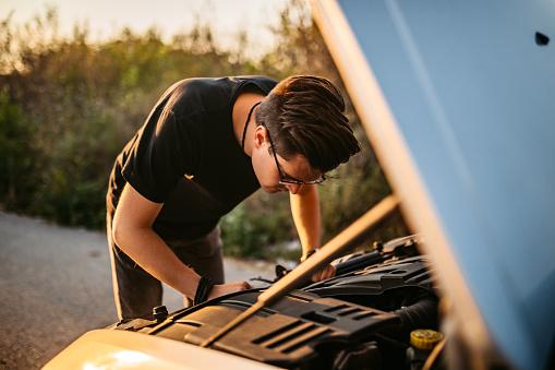 Young Caucasian man repairing his car on road.