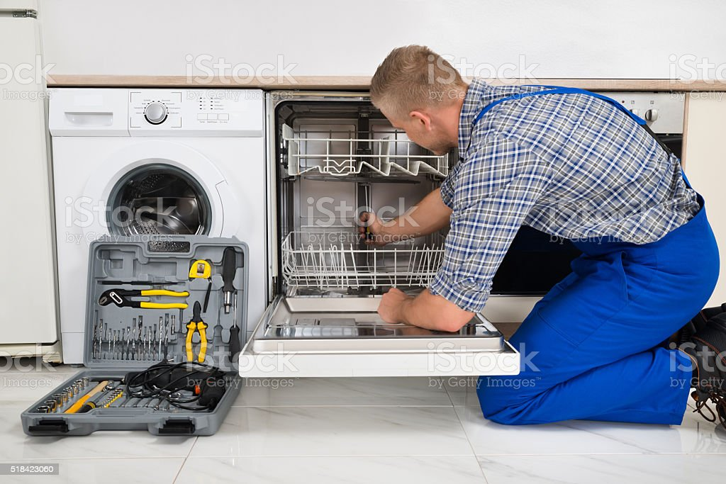 Man Repairing Dishwasher stock photo
