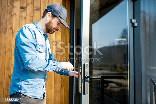 Workman repairing entrance door lock of the modern house or hotel during the sunny weather outdoors