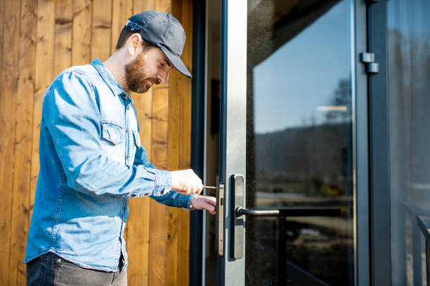 Man repairing door lock Workman repairing entrance door lock of the modern house or hotel during the sunny weather outdoors locksmith stock pictures, royalty-free photos & images