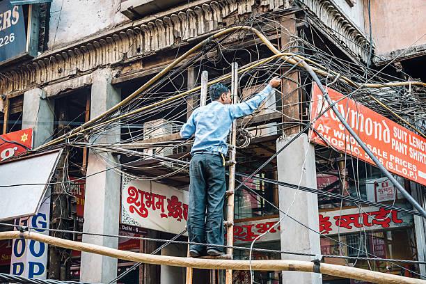 Mann Reparatur der elektrischen Kabeln in den Straßen von Alt-Delhi – Foto