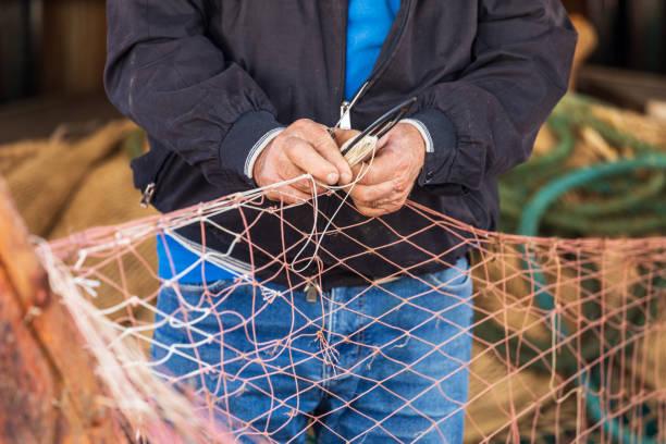 Man repairing fishing nets in the fishing village of Santa Flavia. stock photo