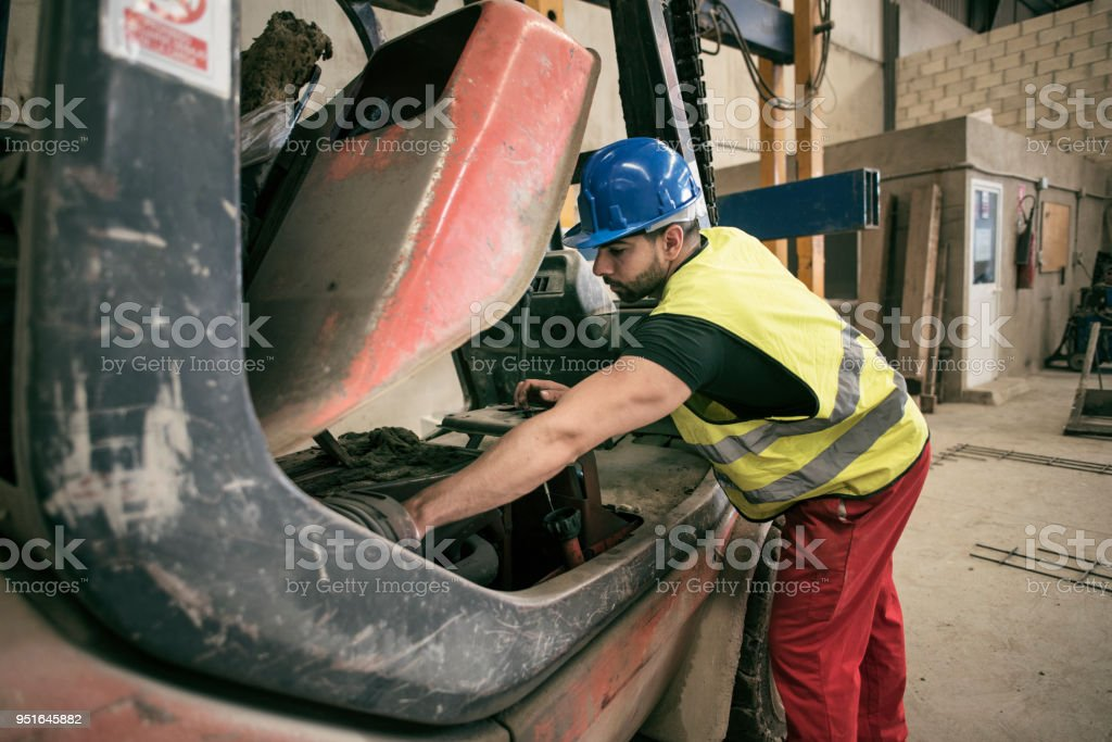 Man repairing forklift in concrete factory stock photo