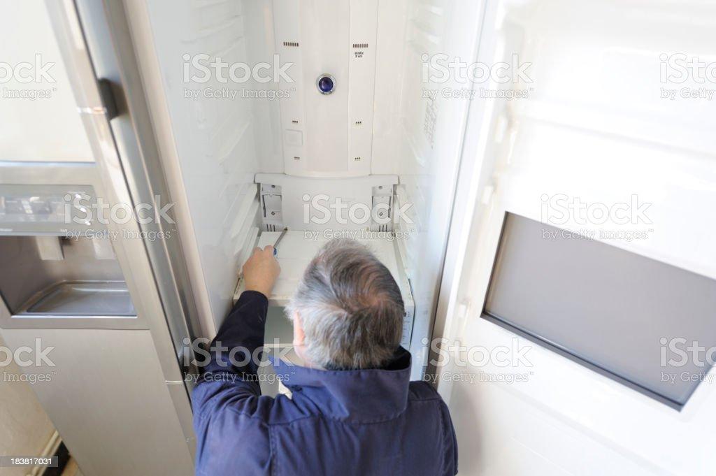 Man repairing refrigerator stock photo