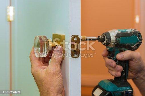 Worker hands installing new door locker man repairing the doorknob closeup