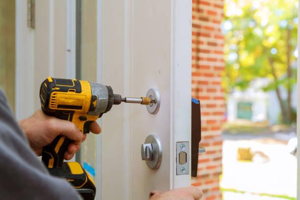 남자는 문 손잡이를 수리. 노동자의 손의 근접 촬영 새로운 문 로커를 설치 - 장인 뉴스 사진 이미지