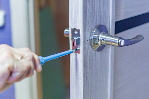 istock man repairing the doorknob with screwdriver. worker's hand installing new door locker 909094076