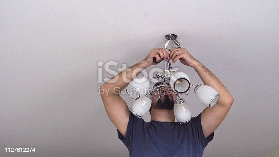 istock A man repairs a chandelier from the ceiling 1127612274