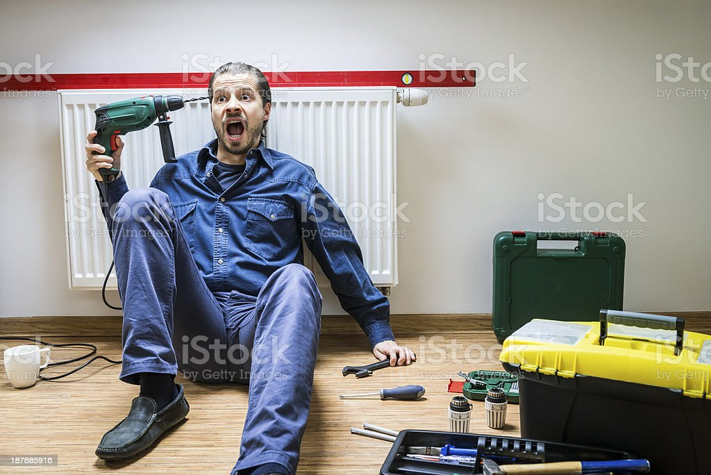 Man repairs heater, he's tired, frustrated, sits under the radiator stock photo
