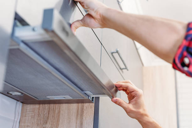 Man repairs hood in kitchen. Replacement filter in cooker hood Man repairs hood in the kitchen. Replacement filter in cooker hood vehicle hood stock pictures, royalty-free photos & images