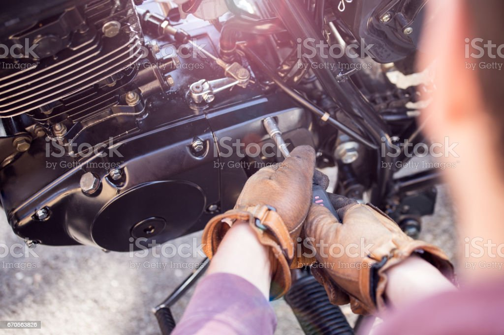 Man repairs motorcycle stock photo