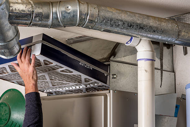 man replaces a filter in a furnace - furnace stock photos and pictures