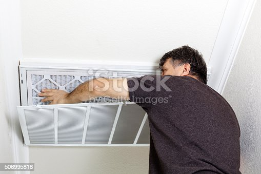 istock Man Replacing Ceiling A/C Filter 506995818