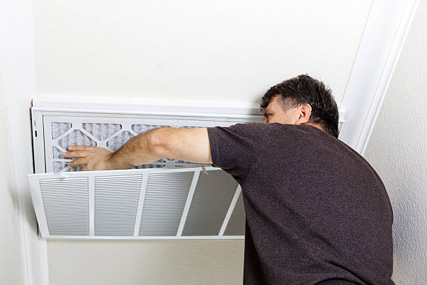 Man Replacing Ceiling A/C Filter stock photo