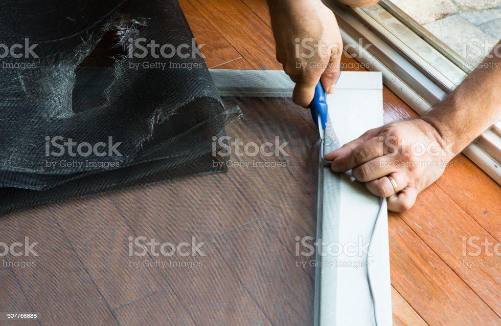 Man replacing ripped old patio door screen stock photo