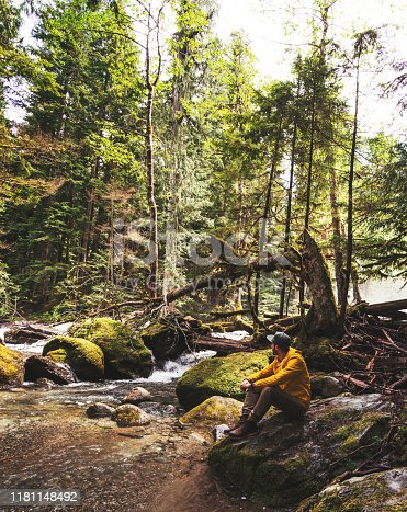Man resting along the river in the forest
