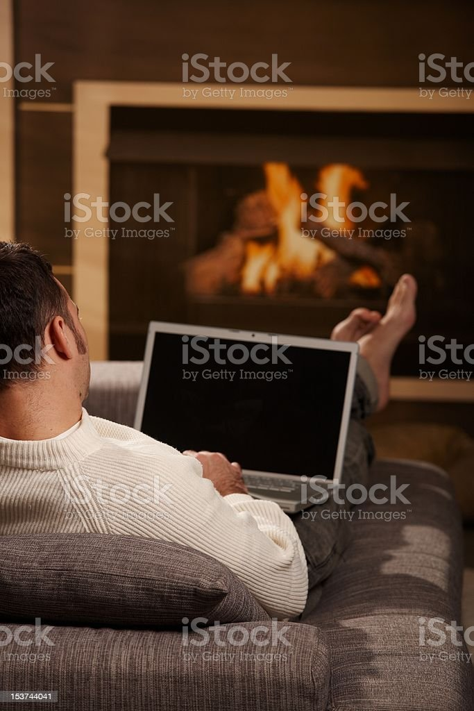 Man resting at fireplace stock photo