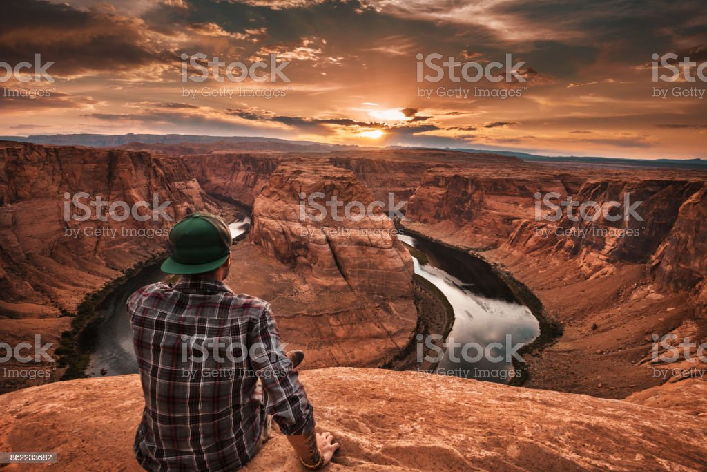 man resting at horseshoe bend in usa stock photo