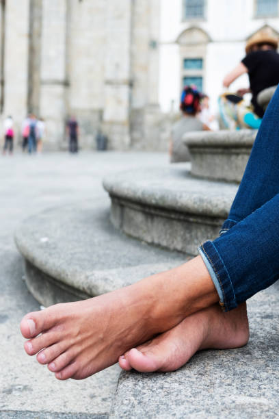 man resting barefoot on the street stock photo