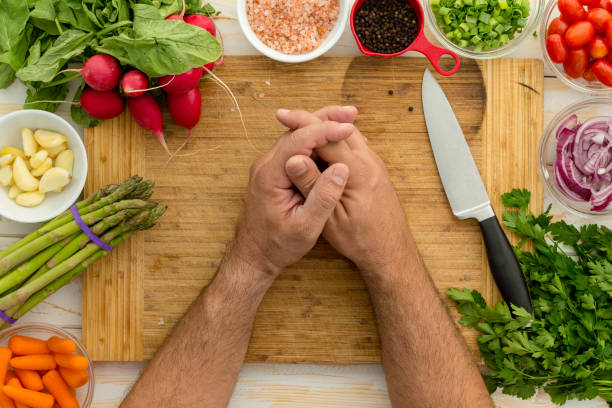 Man resting hands on wooden cutting board stock photo