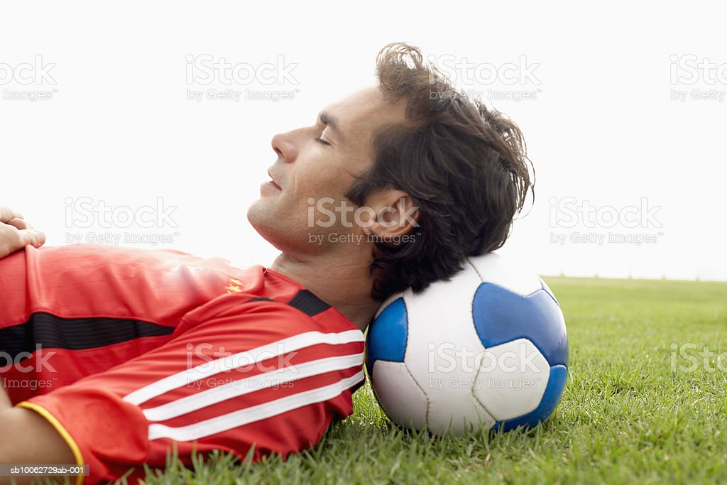 Man resting head on football, eyes closed 免版稅 stock photo