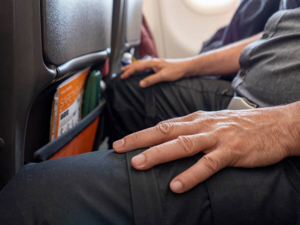 A man resting his hands on his lap as he sits onboard a commercial flight A man resting his hands on his lap as he sits aboard a commercial airline flight. The seat safety buckle is secured across his lap, his knees almost touching the seat in front and his legs apart to make more space for himself, as he sits in the middle seat of a row of seats. He is wearing a grey short sleeved shirt and black trousers. Light is coming in from the nearby cabin window. The aeroplane safety manual and a green glasses case are stored in the pocket of the seat in front of him. midsection stock pictures, royalty-free photos & images