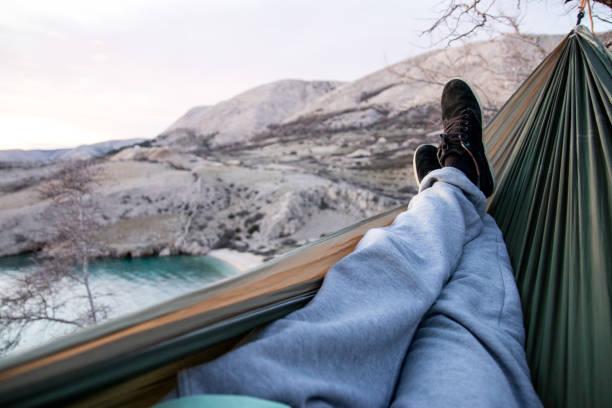man ruht in hängematte durch das meer sicht - sweatpants stock-fotos und bilder