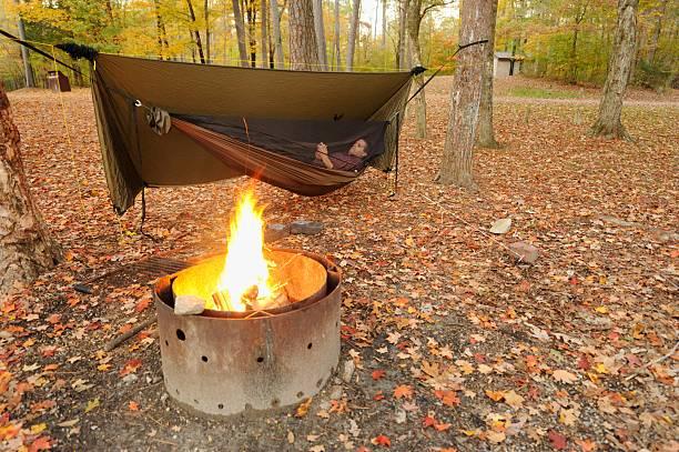 man entspannen in der hängematte mit smart phone durch lagerfeuer - planenzelt stock-fotos und bilder