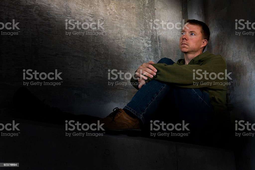 Man resting in rugged surroundings (DEPRESSION SERIES) royalty-free stock photo