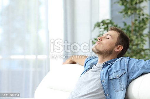 Portrait of a casual tired man resting sitting on a couch at home
