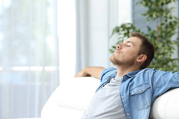 Man resting on a couch at home Portrait of a casual tired man resting sitting on a couch at home tranquil scene stock pictures, royalty-free photos & images