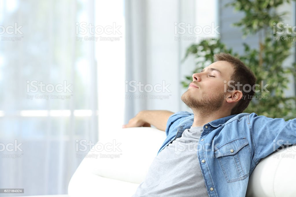 Man resting on a couch at home stock photo