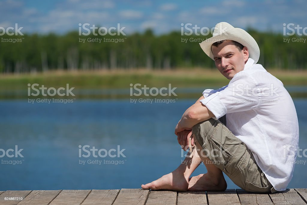 Man resting on nature while sitting on the pier stock photo