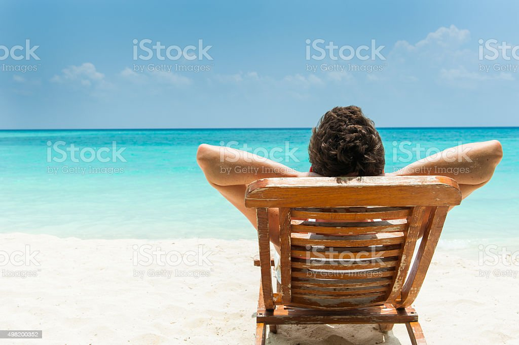 Man resting on the beach stock photo
