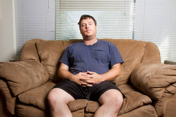 man resting on the couch stock photo