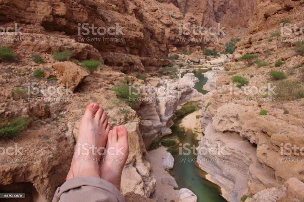 A man resting on the high canyon in Wadi Shab in Oman stock photo