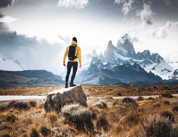 hombre descansa sobre la roca en el chalten - excursionismo fotografías e imágenes de stock