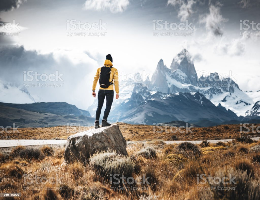 man resting on the rock in el chalten stock photo