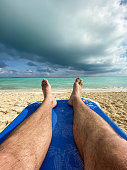 A man is resting on a blue chair on a tropical beach in the Caribbean. He is relaxing and looking at the turquoise colored cristal clear ocean. It is a beautiful sunny summer day. Cayo Coco, Cuba.