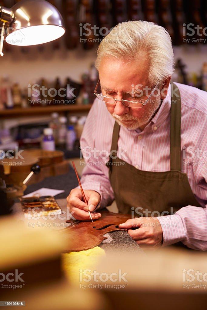 Man Restoring Violin In Workshop stock photo