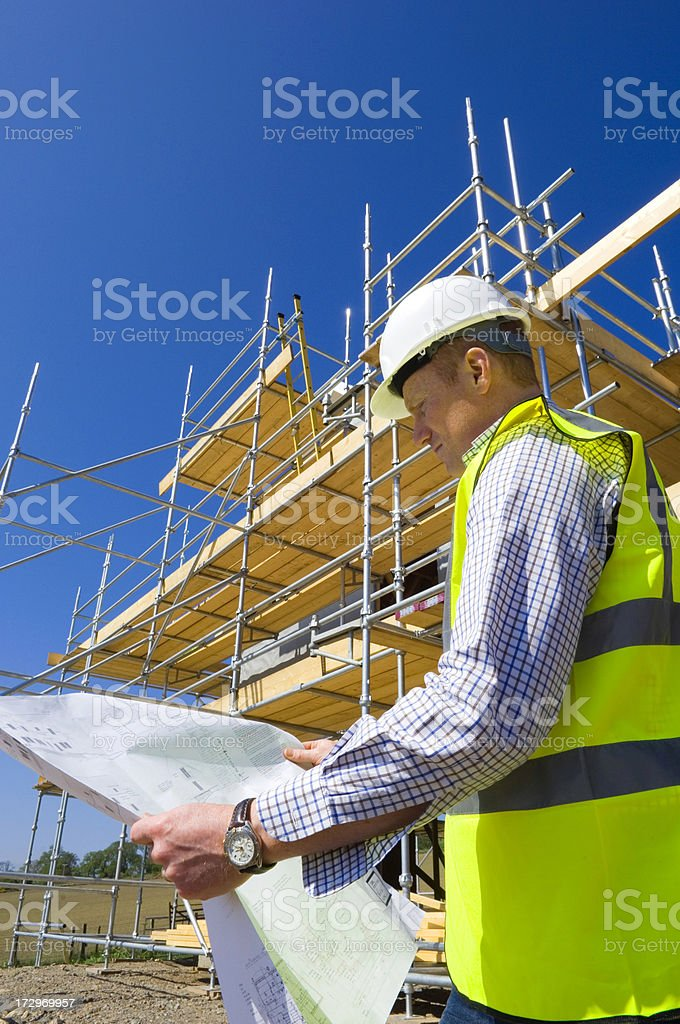 Man reviews building plans on site royalty-free stock photo