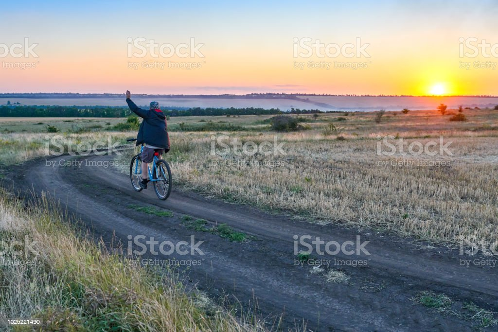 man ride a bike in the country on the field in the evening stock photo