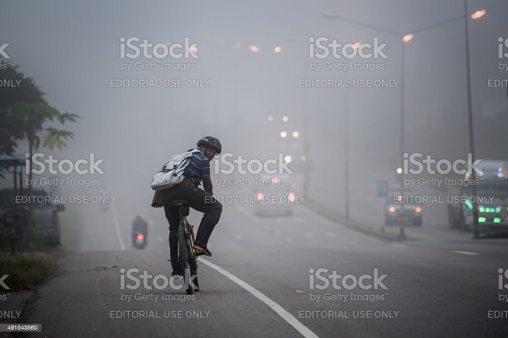 man ride to work in haze stock photo