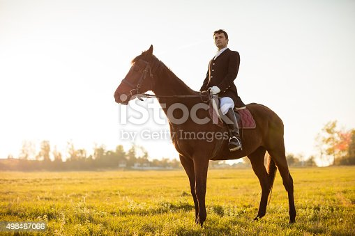 Mature man rides a horse on meadow at sunset and looking away. Man looks very stylish with black tuxedo, black hat, white pants and black leather boots.