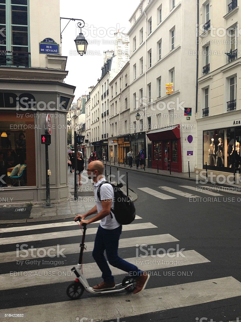 Man rides a scooter in Le Marais stock photo