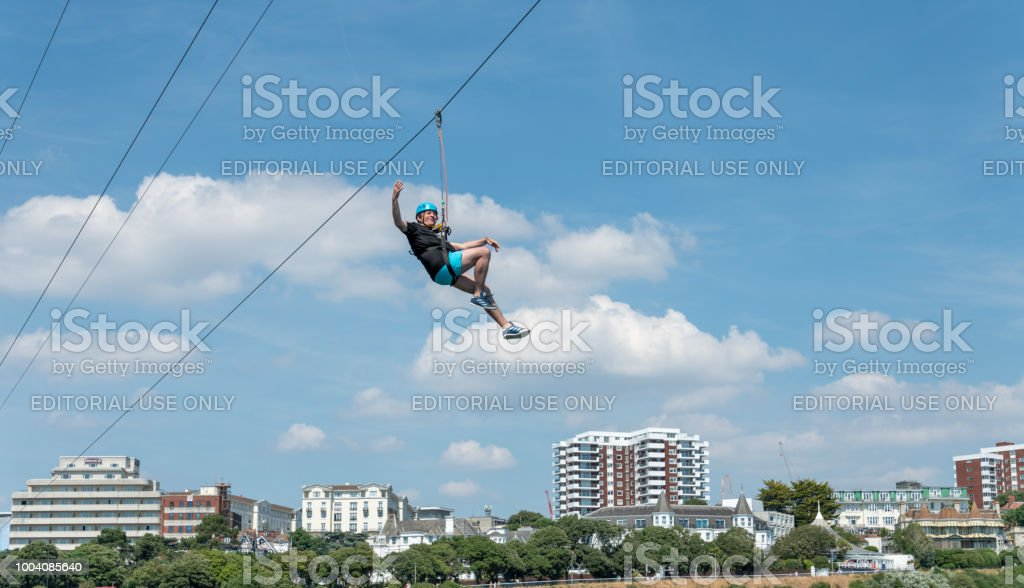 Man rides a zip-wire over the beach in Bournemouth, UK stock photo