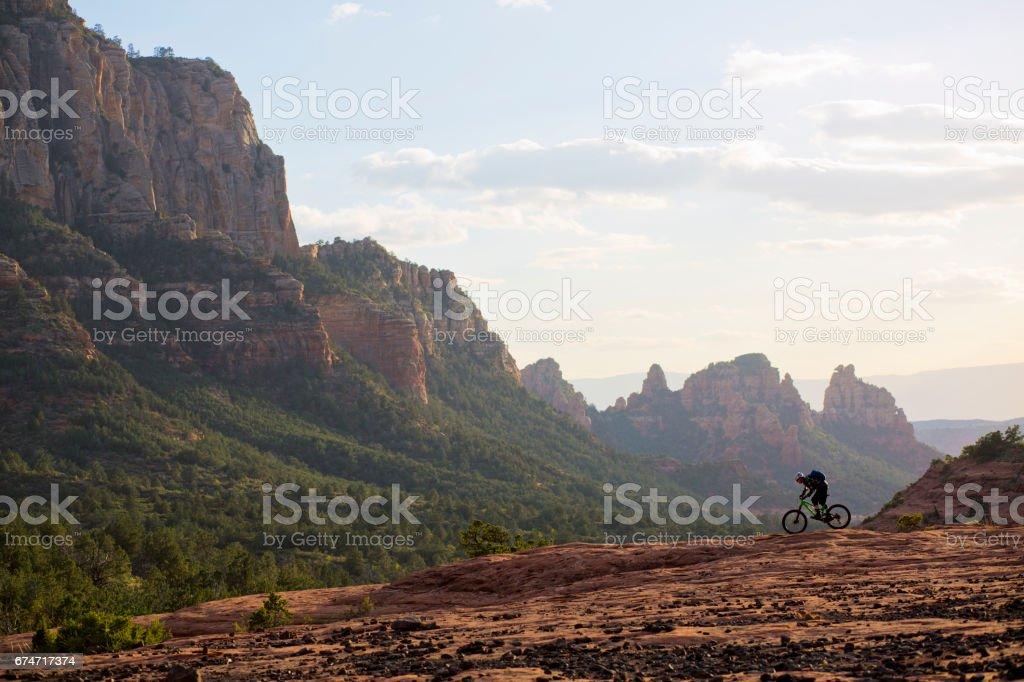 A man rides his enduro-style mountain bike at the end of the day in Sedona, Arizona, USA. stock photo