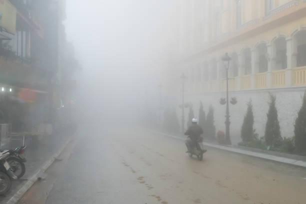 Ein Mann fährt mit seinem Motorrad durch dichten Nebel in der Stadt. – Foto